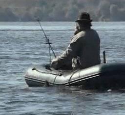 Рыбак в лодке ловит леща